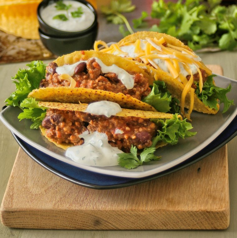 Green chilli con carne tacos with cheddar cheese and sour cream.