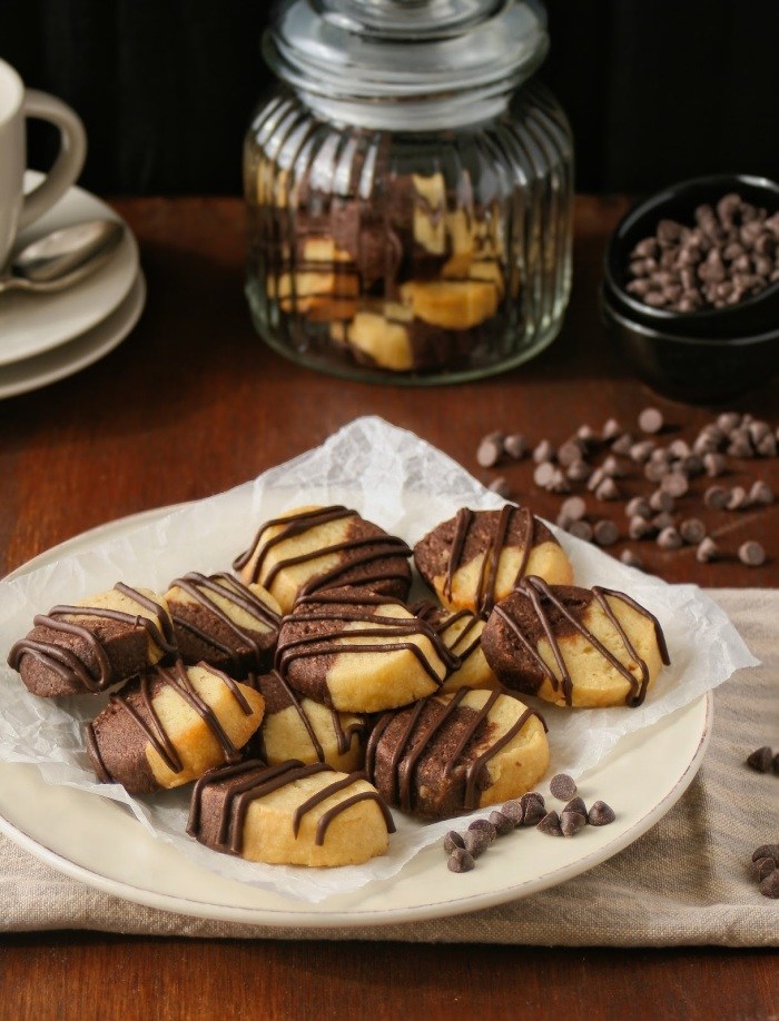 A plate of vanilla and chocolate almond butter cookies drizzled with chocolate.