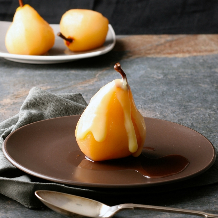 Rosé poached pears in white chocolate sauce.