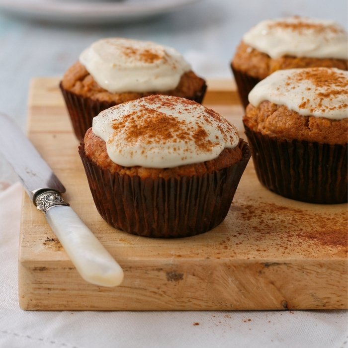 Date, carrot and apple muffins with cream cheese topping.